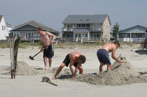 Beach men with shovels.